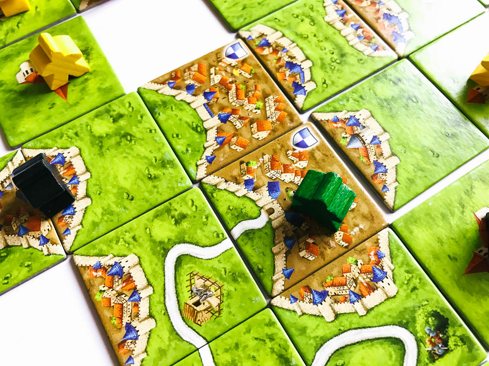A lone green meeple takes charge of a city.