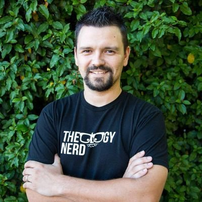 Man with black hair wearing a theology nerd shirt