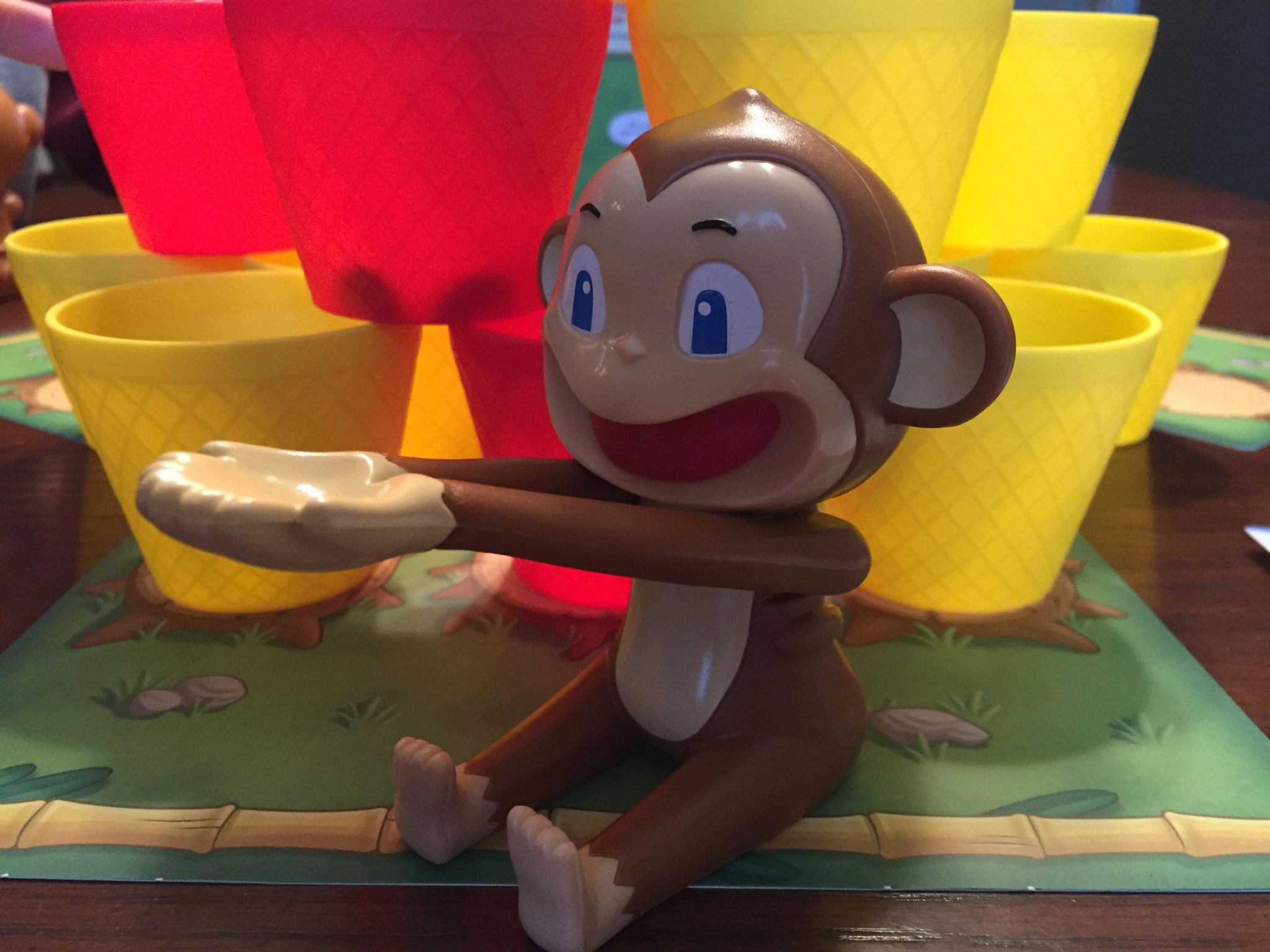A close-up of one of the toy monkeys, with red and yellow cups stacked up behind it.