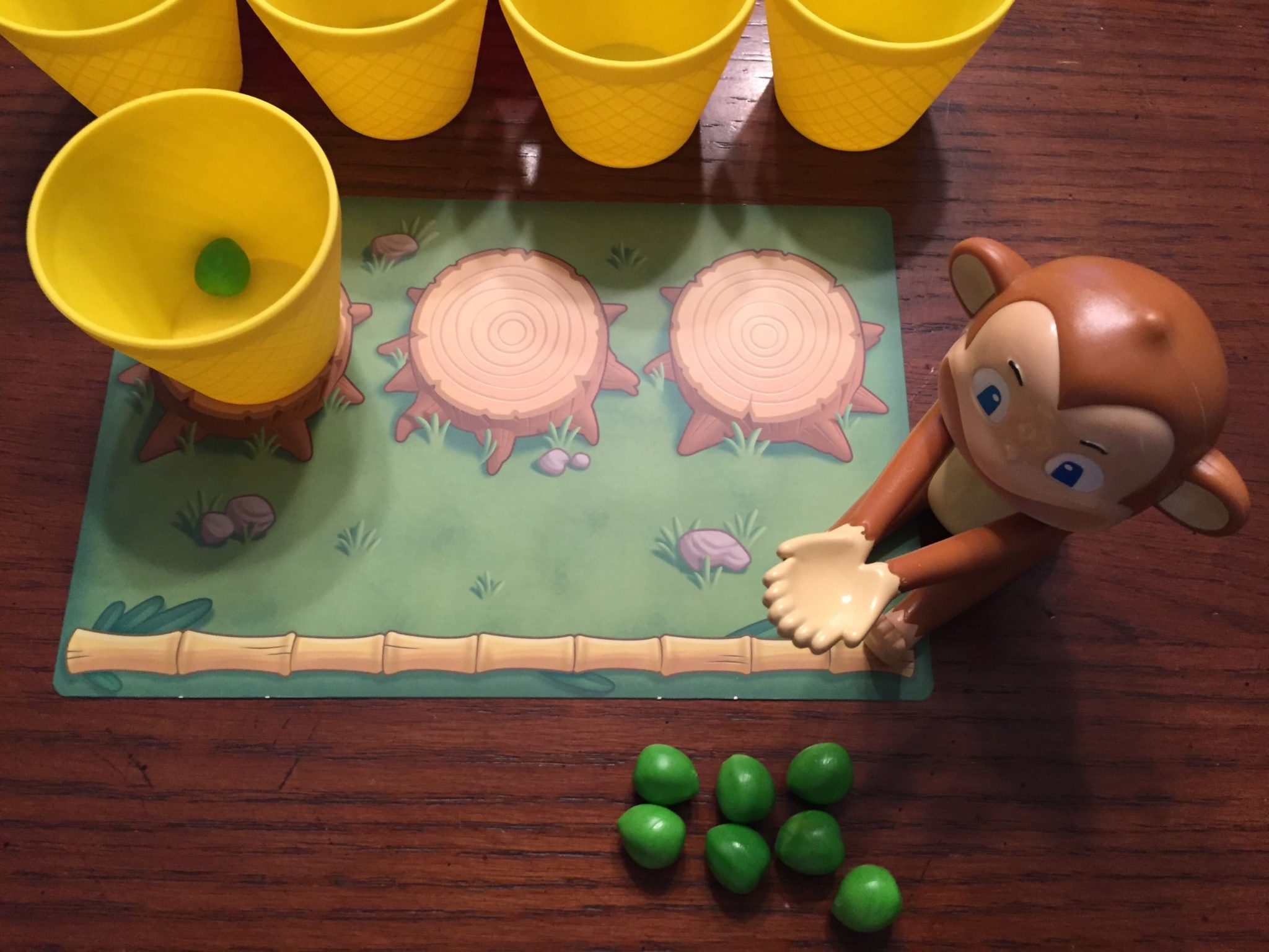 A player's play area is in the center of the photo; they have one yellow cup on the far left stump. A toy monkey and 7 green toy coconuts are in the bottom right.