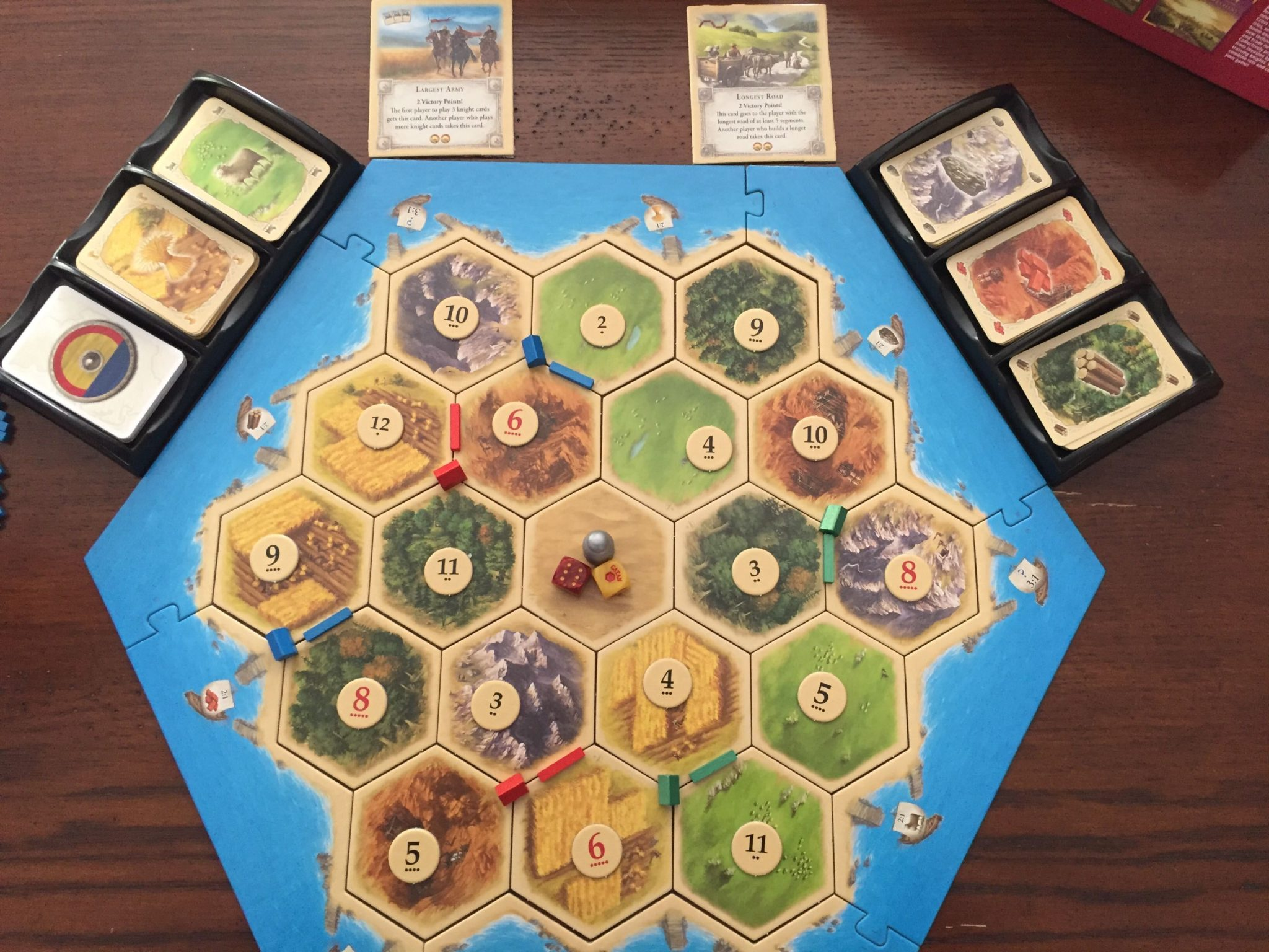 A game of Catan, set up for 3 players. Cards sit in trays at the top of the board.
