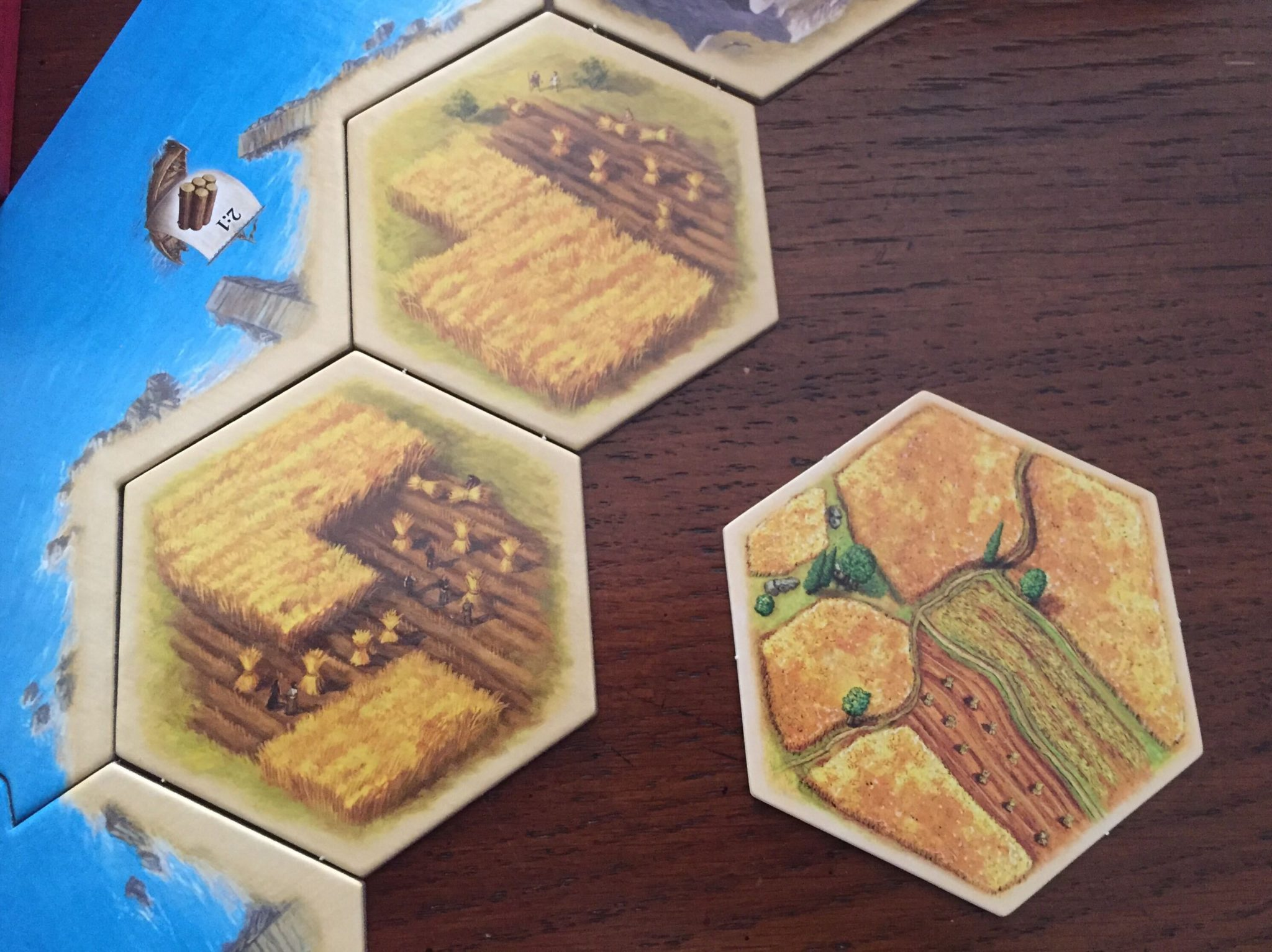 Three Catan Tiles sit in the frame. The two on the left are new art from Catan 25, the one on the right from the original game.  The new art looks more realistic.