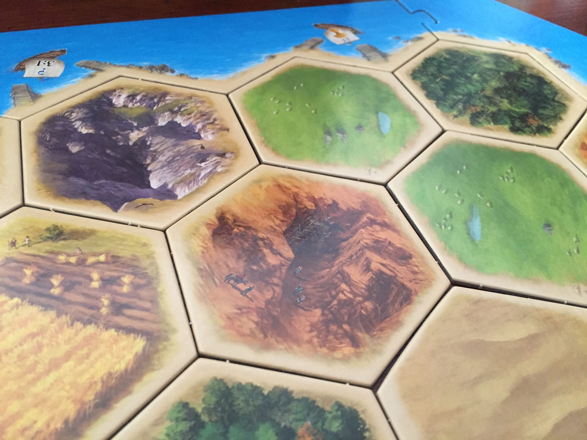 A close-up picture of 6 Catan tiles, one of each type except for two of the sheep-producing fields.