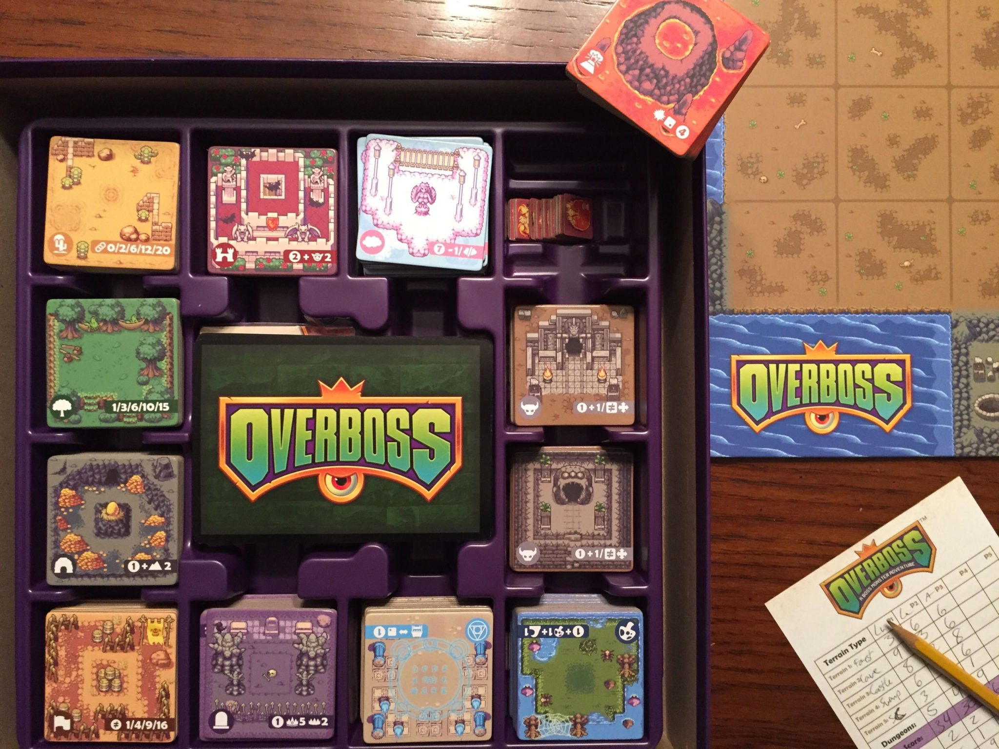 The game insert for Overboss is shown, with all the tiles put away nicely except for the volcano tiles, which are on the edge of the box to show that the volcano monster tiles are stored underneath them.