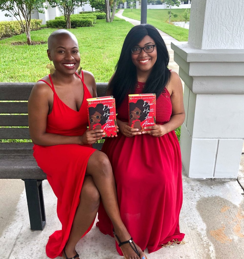 Two black women each holding a book (Presumably these are authors)