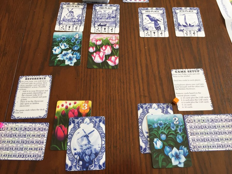 The game is set up for two players; the market is a the top with the blue tulip in 1st and pink in 2nd. The player on the right is starting with a blue card, and the player on the left has a purple card.