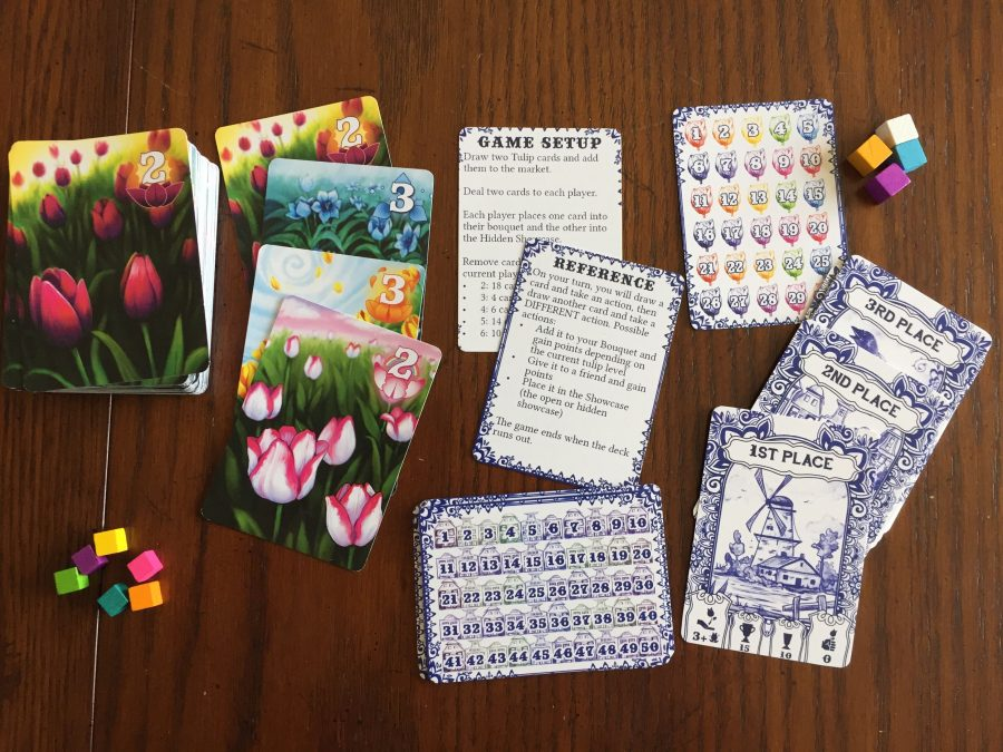 All of the game's components, laid out. Tulip cards are stacked up, but also layered so players can see the four different colors (purple, blue, orange, and pink).