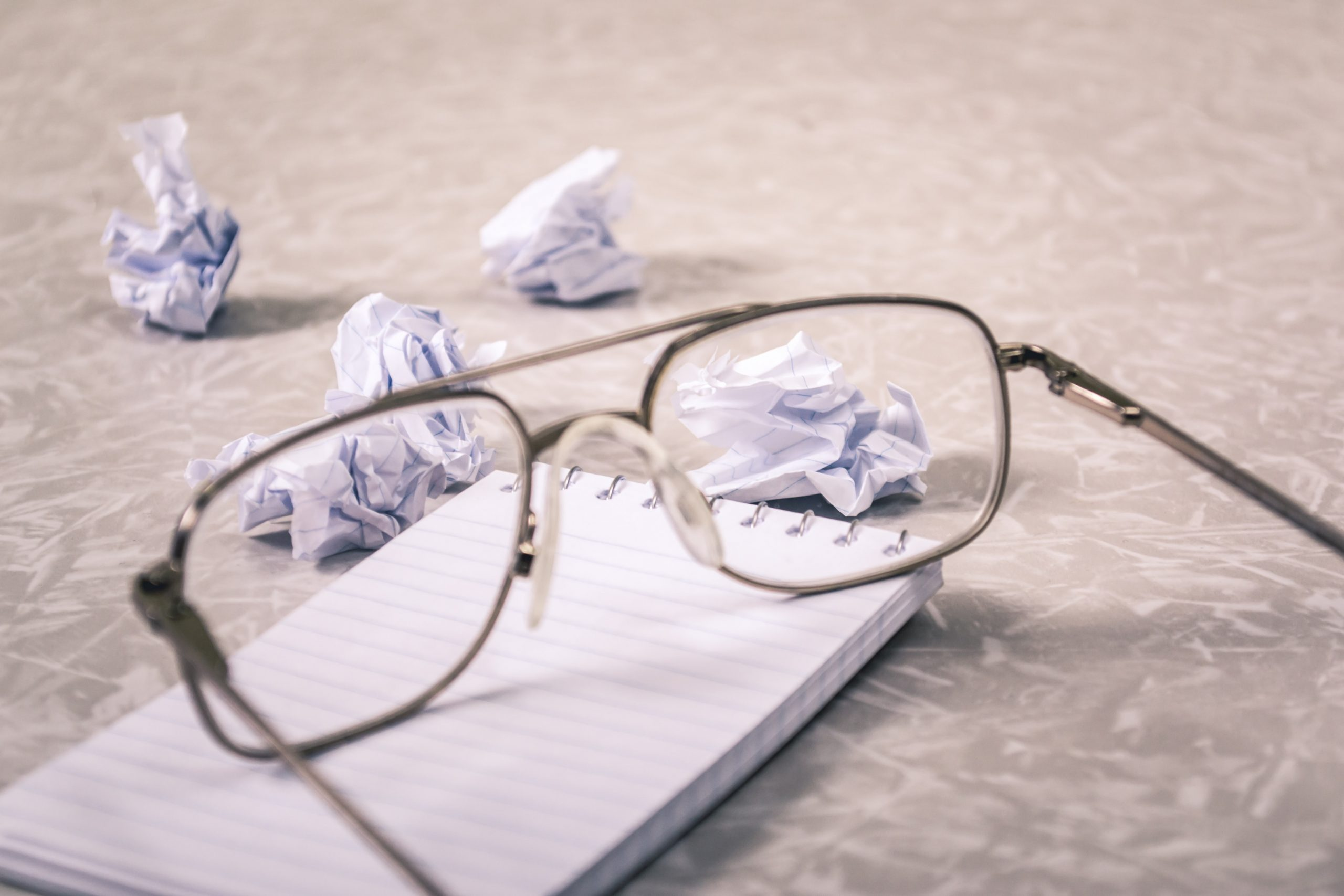 Glasses with a notepad and wads of paper