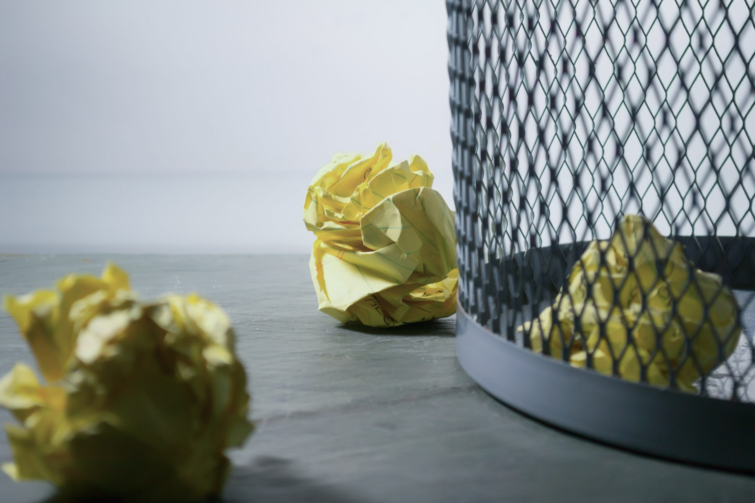 Crumbled paper next to a wastebasket