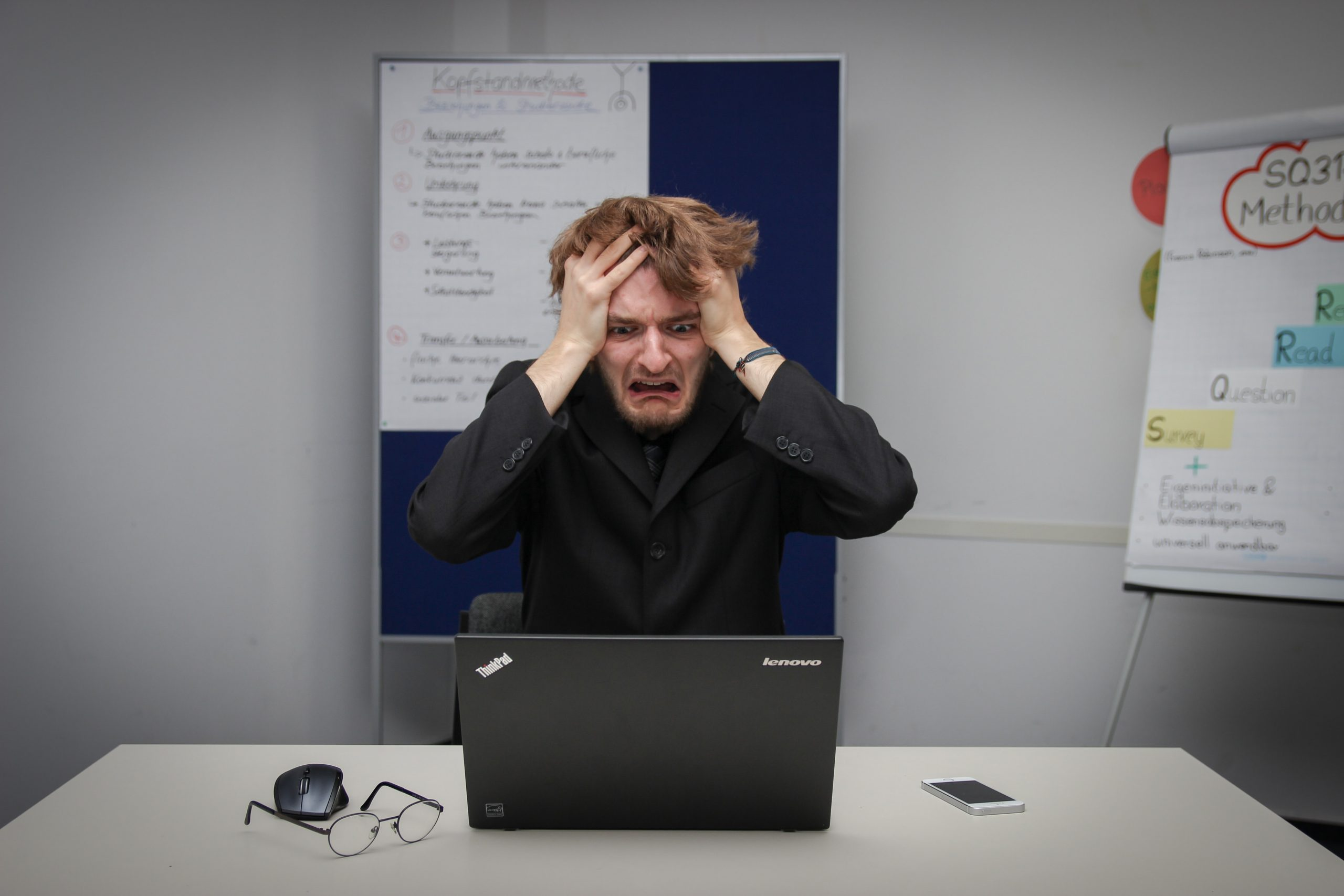 Frustrated man stares at laptop and pulls his hair