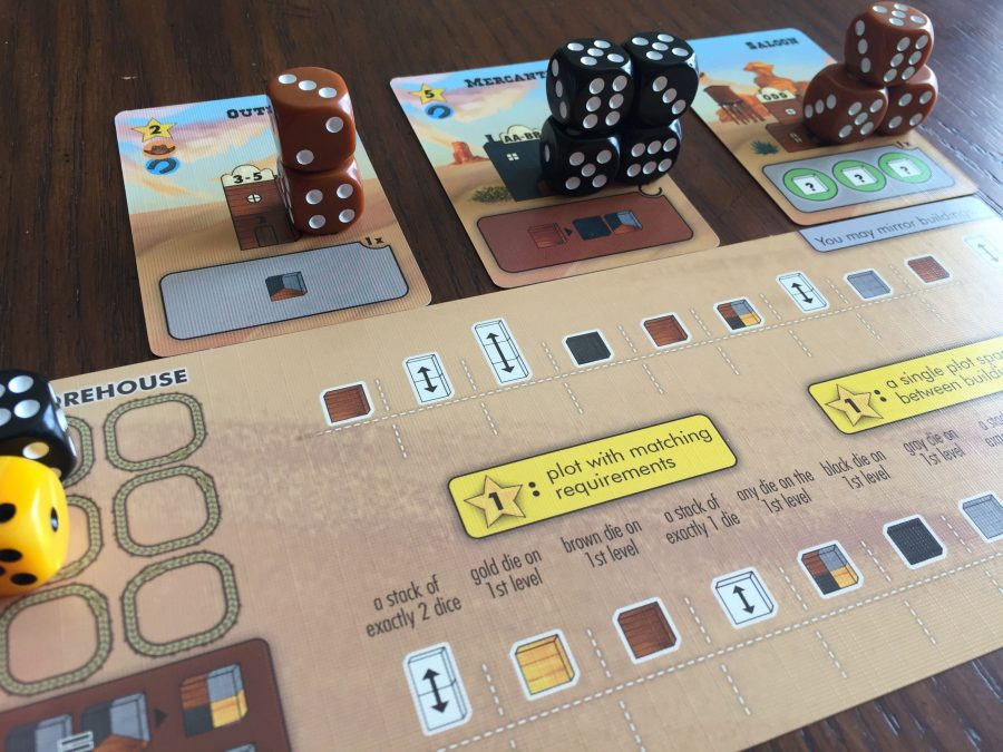 A player's town is shown close up. They have three built buildings - two made out of wood (brown dice) and one made of stone (black dice).