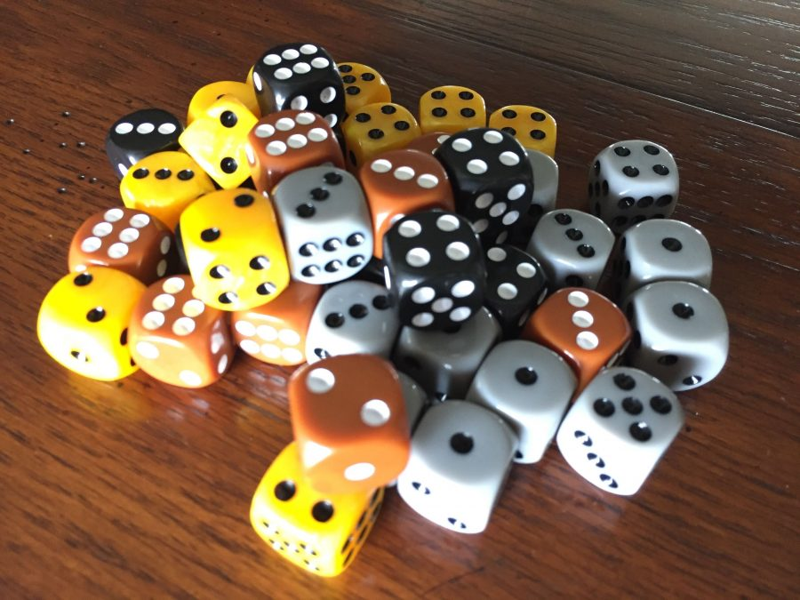 A pile of grey, gold, brown, and black dice, representing half the dice in the game.