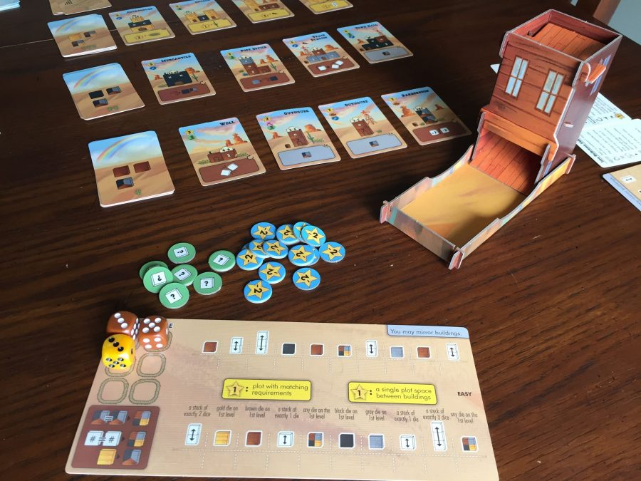 Several game components are laid out. The market is three rows of cards, with 4 cards plus a draw pile. The dice tower is in the corner, and at the bottom of the photo you can see the 2nd player's player board.