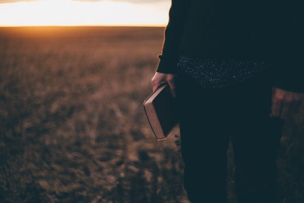 Person standing and holding a Bible, their head is not seen
