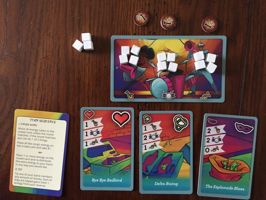 The Starting Setup for the Blue Player. Three $1 tokens are at the top, and underneath that is the Band Card, with four white cubes on the Sax, Trumpet, and Drums. Three white cubes are in reserve just to the left of the card, and underneath the band sits the three starting Song cards and Turn Sequence card.