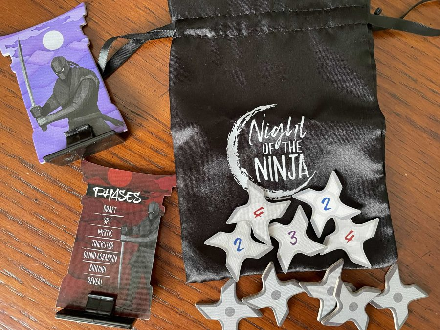 The front and back of the Standees are shown, along with the Honor tokens - which are shaped like throwing stars - laid out on the bag they go in.